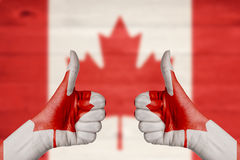 Canada flag painted on female hands thumbs up Royalty Free Stock Photos