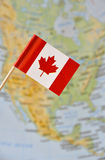 Canada flag pin. Canada paper flag pin, Canada map blurry background (series image Stock Photos