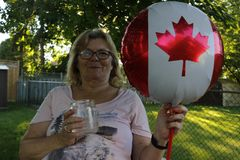 Canada flag. Woman holding Canadian flag. Nice portrait of middle aged lady 40 50 years old with a nationalVisit Canada stock photography