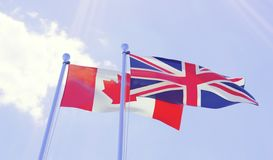 Canada and Great Britain, flags waving against blue sky. Two flags waving against blue sky. 3d image Royalty Free Stock Images