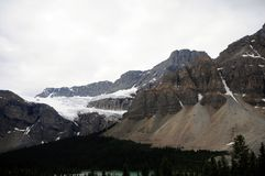Canada Icefield Parkway With Mountain Glacier. Mountain glacier with gray skies fronted by forest and lake traveling Canada Icefield Parkway Stock Photography