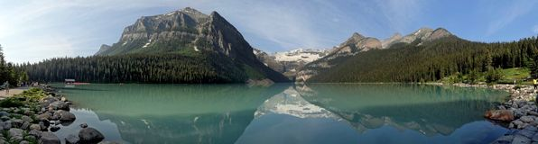 Majestic mountain peaks reflected in the still waters of Lake Louise stock images