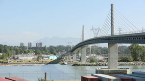 Canada Line Logboom and Train. Early morning as the Canada Line train crosses over the Fraser River from Vancouver entering Richmond while a tug boat towing a stock footage