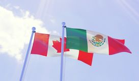 Canada and Mexico, flags waving against blue sky Royalty Free Stock Photography