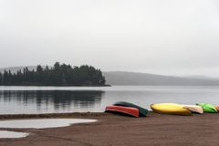 Canada Ontario Lake two rivers grey morning dark atmosphere Canoe Canoes parked beach water in Algonquin National Park. Canada Ontario Lake of two rivers grey Royalty Free Stock Images
