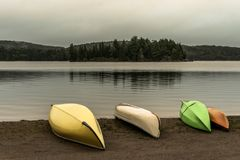 Canada Ontario Lake two rivers grey morning dark atmosphere Canoe Canoes parked beach water in Algonquin National Park. Canada Ontario Lake of two rivers grey Stock Photos