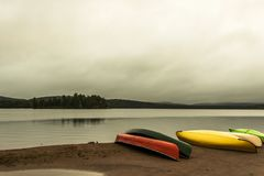 Canada Ontario Lake two rivers grey morning dark atmosphere Canoe Canoes parked beach water in Algonquin National Park. Canada Ontario Lake of two rivers grey Stock Photography