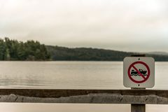 Canada Ontario Lake two rivers grey morning dark atmosphere sign beach no motor boats allowed in Algonquin National Park. Canada Ontario Lake two rivers grey Royalty Free Stock Image
