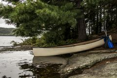 Canada Ontario Lake of two rivers white blank Canoe Canoes parked on island in Algonquin National Park. Canada Ontario Lake two rivers white blank Canoe Canoes Stock Photo