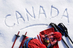 Canada ski vacation concept, word written in snow with skiing equipment Stock Photos