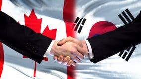 Canada and South Korea handshake, international friendship, flag background. Stock photo stock photos