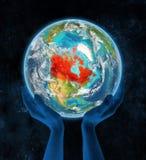 Canada sur terre de planète dans des mains Image stock