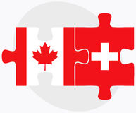 Canada and Switzerland Flags in puzzle isolated on white background Royalty Free Stock Photography