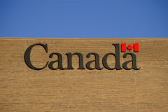 Canada text maple leaf flag writting on brick wall. Canada text inscription maple leaf flag writting pattern of brick wall red and blue sky sunny day Royalty Free Stock Image