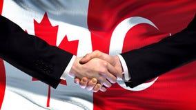 Canada and Turkey handshake, international friendship relations, flag background. Stock photo royalty free stock photo