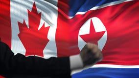 Canada versus de confrontatie van Noord-Korea, vuisten op vlagachtergrond, diplomatie stock video