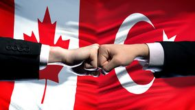 Canada vs Turkey conflict, international relations, fists on flag background. Stock photo stock images