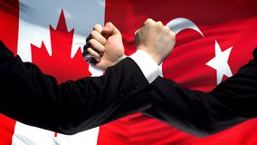 Canada vs Turkey confrontation, countries disagreement, fists on flag background. Stock photo stock image