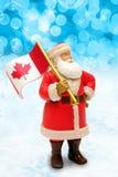 Canadense Santa Claus que guarda a bandeira de Canadá fotografia de stock royalty free