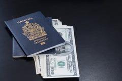 Canadese die paspoorten met de dollarsbankbiljetten van Amerikanen zijn binnengegaan in stock foto