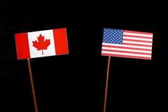 Canadese vlag met de vlag van de V.S. op zwarte stock foto