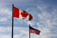 Canadian and American flag on blue sky Royalty Free Stock Photos