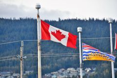 Canadian and British Columbian flags proudly waving in the sky. royalty free stock image