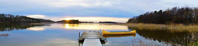 Canadian canoe in lake at sunset. Panoramic view with yellow canadian canoe in lake at sunset Royalty Free Stock Photos