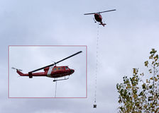 Canadian Coast Guard Helicopter slinging Cement Bucket. A Canadian Coast Guard Bell 212 Twin Huey helicopter in service transporting fresh concrete to an Royalty Free Stock Photography