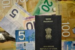 Canadian currency of denomination 5, 10, 20, 100 with Indian Passport. Canadian currency dollars of denomination 5, 10, 20, 100 with Indian Passport royalty free stock photo