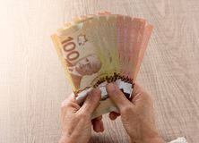 Canadian currency. Dollars. Above view of old retired person paying in cash. Canadian currency. Dollars. Money from Canada. Above view of old retired person royalty free stock photos