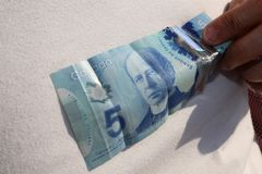 A close up of man`s hand and Canadian money- $5.00 bill. Canadian $5.00 currency. This picture can be used as a magazine front cover or billboard for anything to stock photos