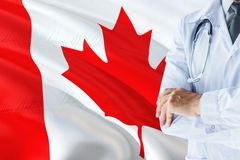 Canadian Doctor standing with stethoscope on Canada flag background. National healthcare system concept, medical theme stock photos