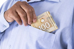 Canadian dollar banknotes. Holding and keeping Canadian dollar banknotes to pocket Stock Photo