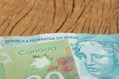 Canadian Dollars and Brazilian currency. Close up of cash bills on rustic wood table. Canadian Dollars and Brazilian currency. Money from Canada and Brazil royalty free stock image