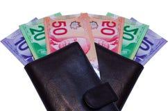 Canadian Dollars In Brown Wallet. Ten, twenty and fifty Canadian dollars in brown leather wallet. Isolated in white background Royalty Free Stock Image