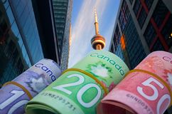 Canadian Dollars With CN Tower Background. Canadian money rolls with Cn tower and skyscraper background. Horizontal photo Stock Photo