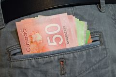 Canadian Dollars in jean pants pocket. There are fifty, twenty and ten canadian dollars in man`s gray jean pants pocket Stock Image