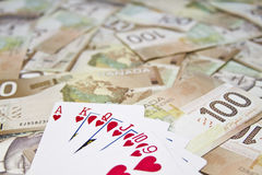 Canadian dollars and royal flush hand Stock Image