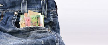 Canadian dollars of value 20, 50 and 100 in Blue Denim Jeans Pocket, Concept on earning money, saving money Royalty Free Stock Photos