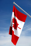 Canadian Flag. Red and white Canadian flag hanging against blue sky and white wispy clouds royalty free stock images