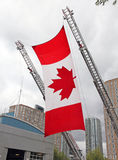 Canadian Flag. Hangs on two fire truck ladders in a memorial ceremony Royalty Free Stock Photo