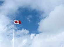Canadian Flag. The maple leaf flies high against a background of fluffy clouds royalty free stock photos
