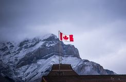 Canadian flag against snowy rocky mountain. Canada flag in banff national park royalty free stock photography