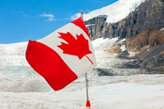 Canadian flag on athabasca glacier with sun royalty free stock photography