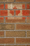 Canadian Flag on Brick Wall. A faded Canadian flag painted on the surface of a brick wall stock images