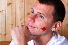 Canadian flag on the face of young man Stock Photos