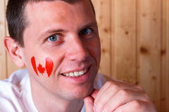 Canadian flag on the face of young man Stock Photo