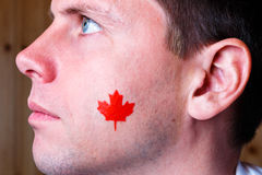 Canadian flag on the face of young man Stock Images