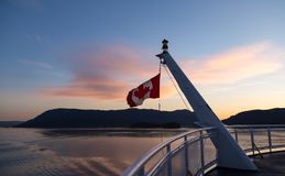 Canadian flag on a ferry at sunset royalty free stock image